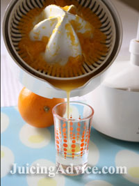 Pouring fresh juice from an electric citrus juicer.