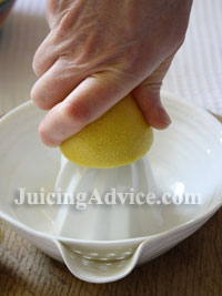 Using a ceramic hand juicer to juice a citrus fruit