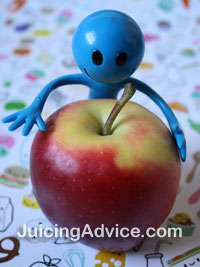 A childs toy holding an apple for juicing