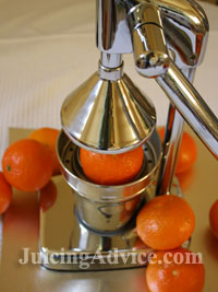 Juicing with a manual orange juicer.