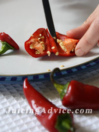 Chopping red chilli as part of a vegetable juicing recipe.