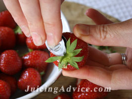 Removing strawberry stalks for one of the  free juicing recipes.